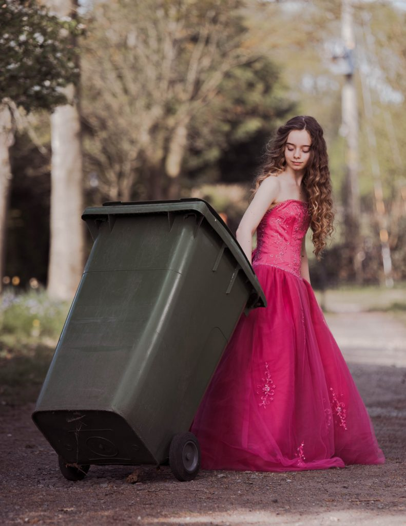 Girl wearing a pink prom dress photographed taking out the rubbish