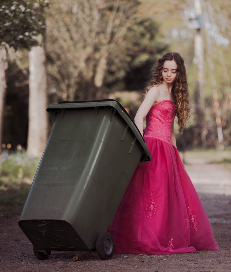 Girl wearing a pink prom dress photographed doing the gardening